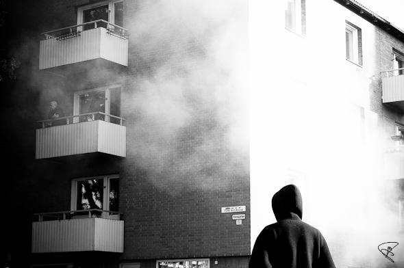 män betraktar brand i hyreshus Flen